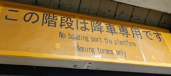"""東京の渋谷駅構内の看板(2018年1月撮影)。上段には「この階段は降車専用です」とあり、下段1行目には""""<em>No bouding port the plantform</em>""""、2行目に""""<em>Amoing torans only</em>"""" と記されている。"""