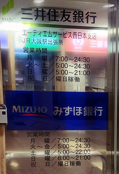 大阪駅のATMコーナー(2017年9月撮影)。三井住友銀行とみずほ銀行のATMの営業時間が表示されており、祝日についてはいずれも「曜日稼働」と記されている。