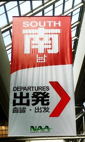 """成田空港第2ターミナル出発ロビーにつるされている案内(2017年10月撮影)。""""南""""が日本語と中国語を表している。"""